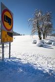 Cartello stradale avverte di neve e ghiaccio, giorno soleggiata e innevata, con — Foto Stock