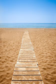 Wooden path to the sandy beach — Stock Photo