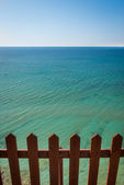 Wooden fence in front of beautiful turquoise and calm sea on Cor — Stock Photo