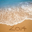 Year 2014 written in sand on tropical beach — Stock Photo
