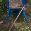 Blue wheelbarrow full of dried grass and rakes - 图库照片