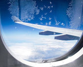 Ice flowers on airplane window — Stock Photo