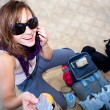 Stock Photo: Young girl smiling while packing for travel