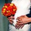 Wedding bouquet in bride's hand, with groom's hands around her — Stock Photo