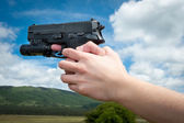 Woman's hand holding gun, isolated — Stock Photo