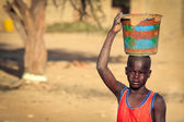 Unidentified boy carrying clay in wooden vessel on his head, — Stock Photo