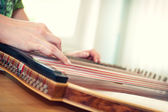 Close up of young girl's hand playing on zither — Stock Photo