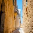 Typical tight street in Mdina, Malta, with high stone walls of h — Stock Photo