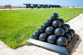 Old cannonballs stacked in pyramid, in front of cannons, on Valletta Castle, Malta — Stock Photo