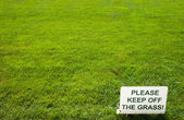 Please keep of the grass lettering sign on green background — Stock Photo