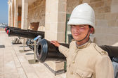 Boy dressed as in old English military uniform in front of the cannons in Valletta, Malta — Stock Photo