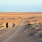 Постер, плакат: Johan Steene and Joao Oliveira winners of extreme endurance marathons Transomania 2014 beginning the last stage of desert run