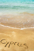 Cyprus written in sand on beach with sea in background — Stock Photo