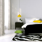 Black and white bed and a yellow lamp — Stock Photo