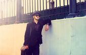 Elegantní muž v klobouku, stojící u zdi — Stock fotografie