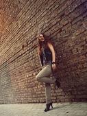Söt tjej med rött hår stå nära tegelvägg — Stockfoto