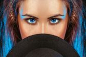 Woman with blue eyes behind the hat — Stock Photo