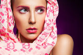 Portrait of female in scarf on purple background — Stock Photo