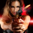 Attractive woman shooting from golden gun — Stock Photo