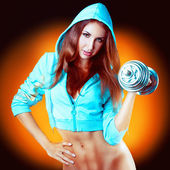 Inflated girl with dumbbells in a sports jacket — Stock Photo