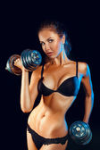 Hot sports girl woth dumbbells looking at camera — Stock Photo