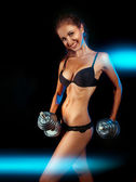 Sports female with dumbbells and toothy smile — Stock Photo