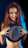 Shy girl hiding boobs behind a hat — Stock Photo