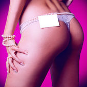 Square photo of female ass in white panties and empty name tag — Stock Photo