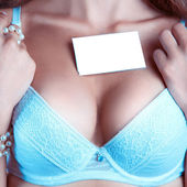 Woman's breast in a bra with empty name tag — Stock Photo