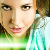 Beautiful girl looking at camera in studio with green line on ph — Stock Photo