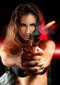 Attractive woman shooting from golden gun — Stock Photo