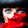 Lovely brunette behind red rose in studio — Stock Photo #29099365