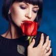Attractive female with closed eyes and red rose — Stock Photo #29099437