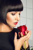 Gorgeous adult brunette with red rose on gray background in stud — Stock Photo