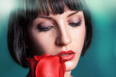 Horizontal portrait of cutie brunette with red rose — Stock Photo