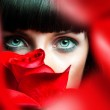 Lovely brunette behind red rose in studio — Stock Photo #29569863