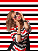 Young woman in sunglasses on stripes background — Stock Photo