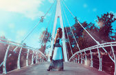 Photo of funny woman on bridge with dog behind — Stock Photo