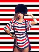Pretty girl in furhat on stripes background — Stock Photo