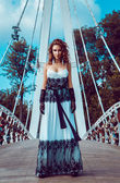 Red hair girl stand on bridge outdoors — Stock Photo