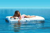 Elegant girl lying on bed in open sea — Stock Photo