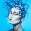 Stock Photo: Attractive female with creative body art and hairstyle on blue b
