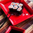 Japanese roll with salmon on red plate — Stock Photo #40905319