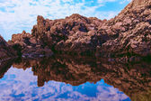 Horizontal picture of rocks and their reflection in the sea — Stock Photo