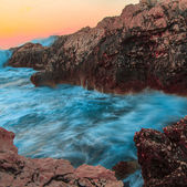 Raging ocean waves breaking on rocks at sunset — Stock Photo