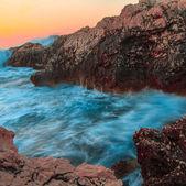 Raging ocean waves breaking on rocks at sunset — Stock Photo