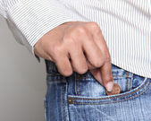 Person taking a penny from jean pocket — Stock Photo