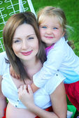 Young pregnant woman with daughter — Stock Photo
