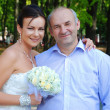 Bride posing for the camera with her father - Stock Photo