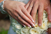 Hands of bride and bridegroom with rinds — Stock Photo